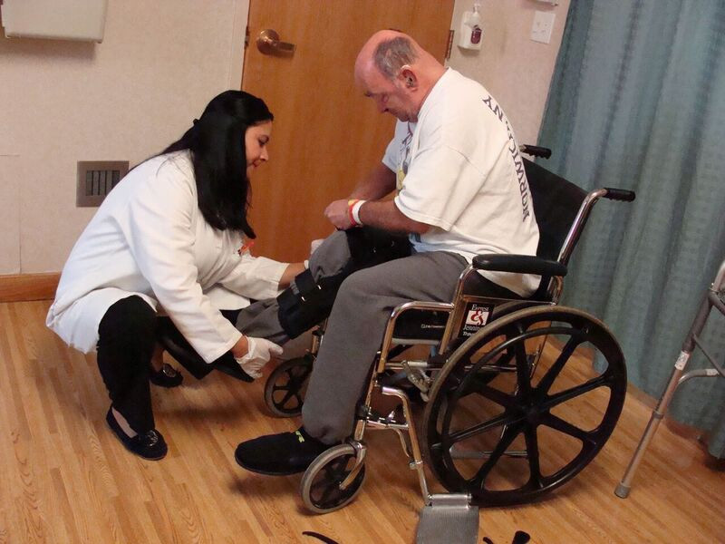 physical therapist helping man get out of wheelchair