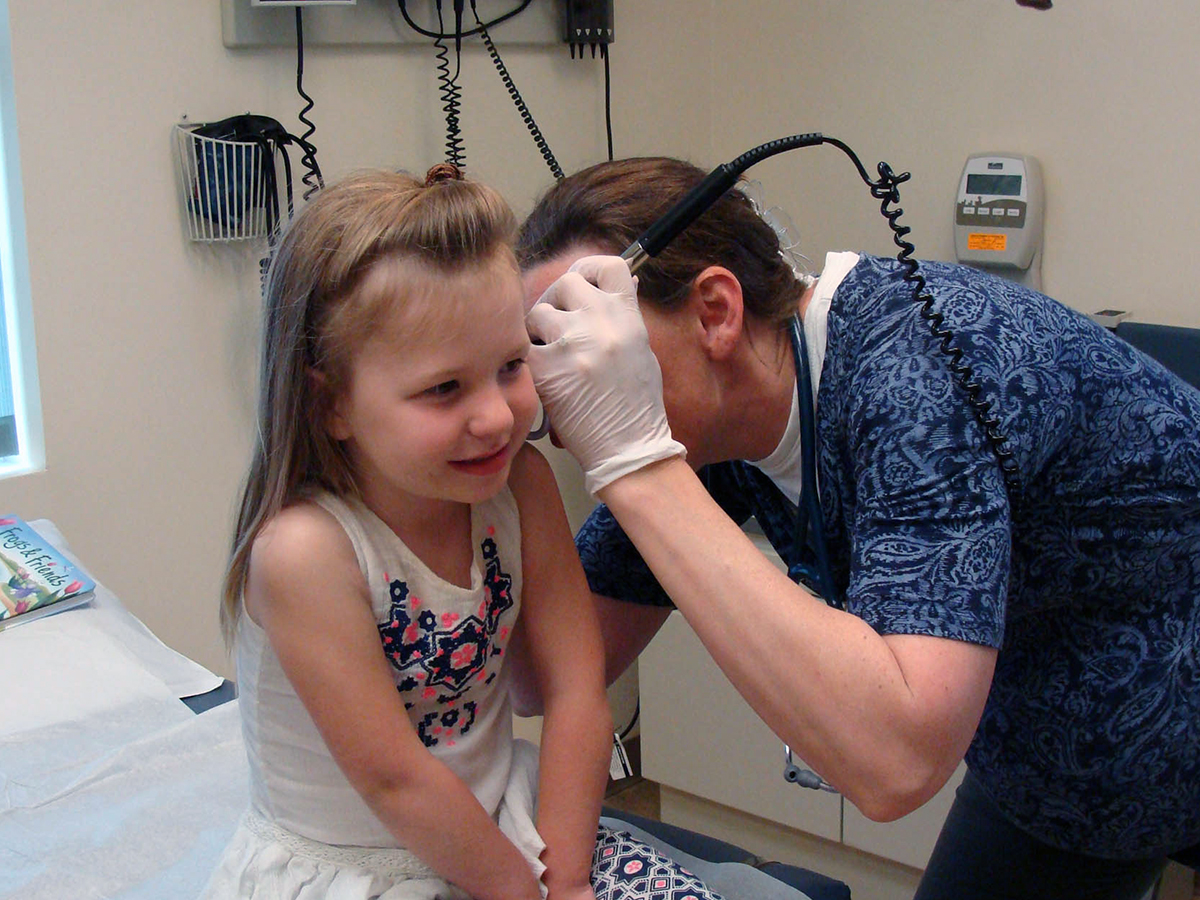 doctor checking young girls ear